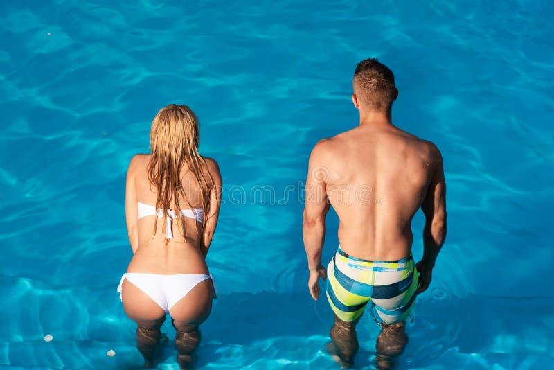 Couples tropicaux Beau jeune homme et femme détendant sur la plage Couplez les loisirs actifs - concept de piscine sexy photo stock