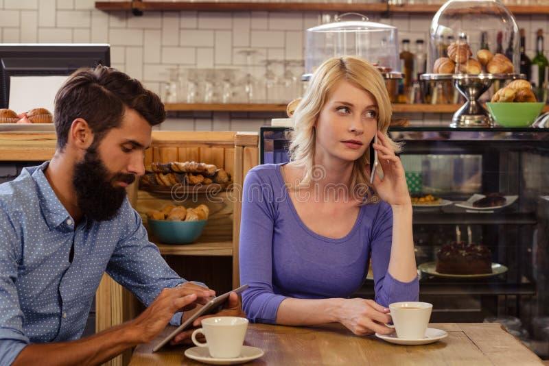 Couples utilisant des smartphones avec un phonecall photo stock