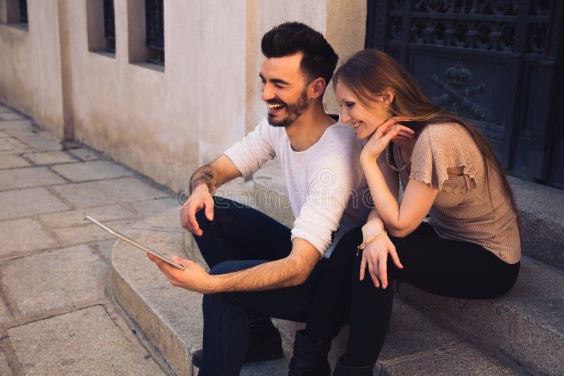 Couples utilisant l'ipad numérique de comprimé et rire dans la rue images stock