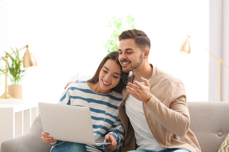 Couples utilisant l'ordinateur portable pour la causerie visuelle photo stock