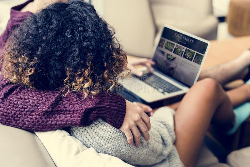 Couples utilisant l'ordinateur portable se reposant ensemble sur le divan photo libre de droits