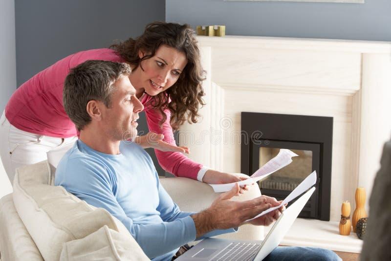 Couples utilisant l'ordinateur portatif et discuter des factures de ménage photo libre de droits