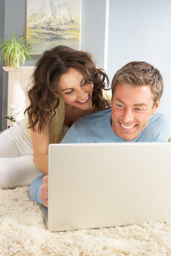 Couples utilisant la pose de détente d'ordinateur portatif sur la couverture à la maison image stock