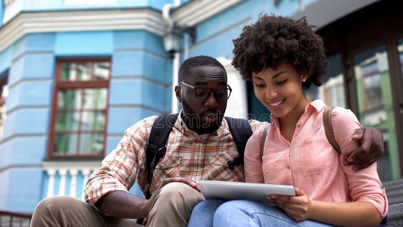 Couples utilisant le comprimé d'application de guide de voyage, programme d'enseignement pour des étudiants photos libres de droits