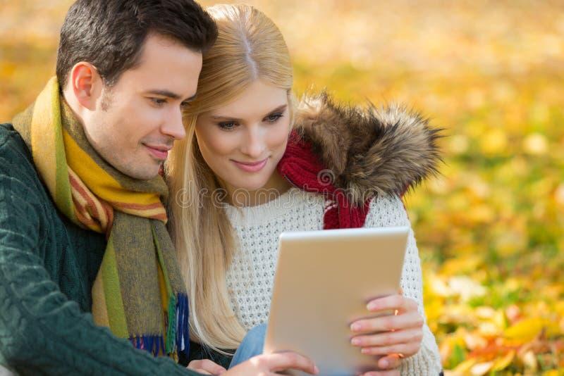 Couples utilisant le comprimé numérique en parc pendant l'automne images libres de droits