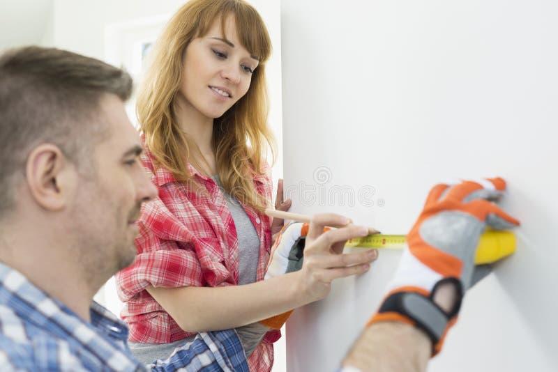 Couples utilisant le ruban métrique sur le mur images libres de droits