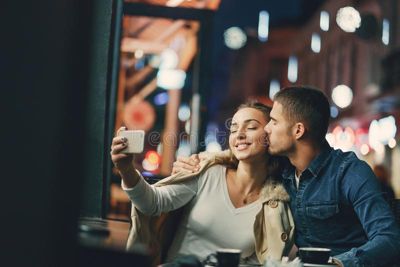 Couples utilisant le téléphone dans un café photos libres de droits