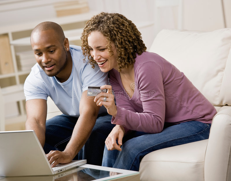 Couples utilisant par la carte de crédit à faire des emplettes en ligne photos stock