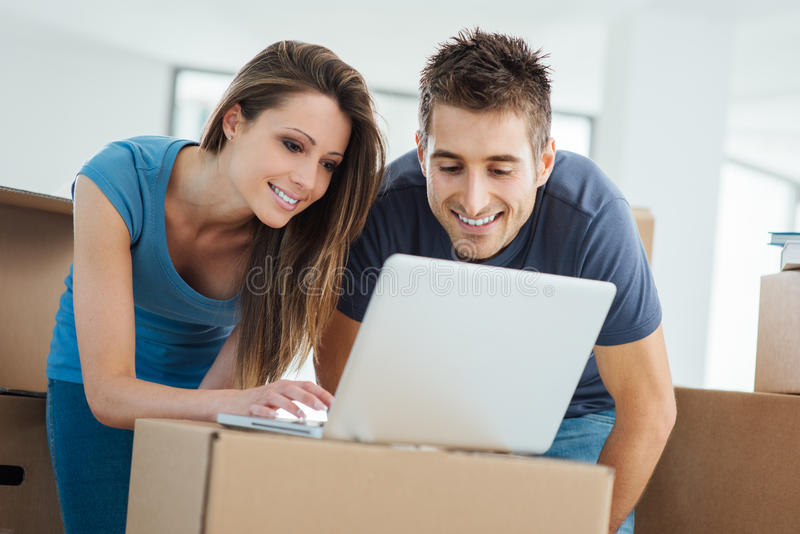 Couples utilisant un ordinateur portable dans leur nouvelle maison photo stock