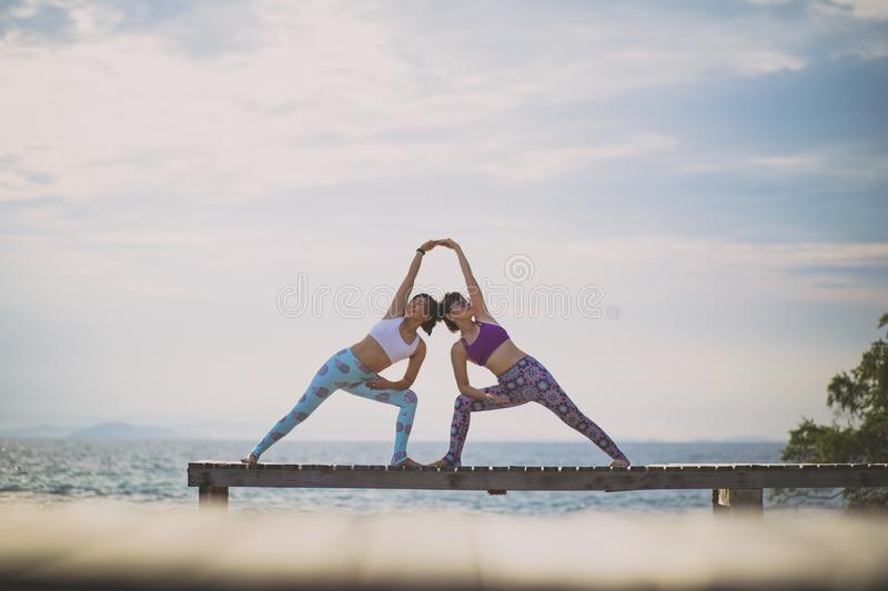 Couples of woman playing yoga pose on beach pier with moring sun light. Couples of women playing yoga pose  on beach pier with moring sun light stock images