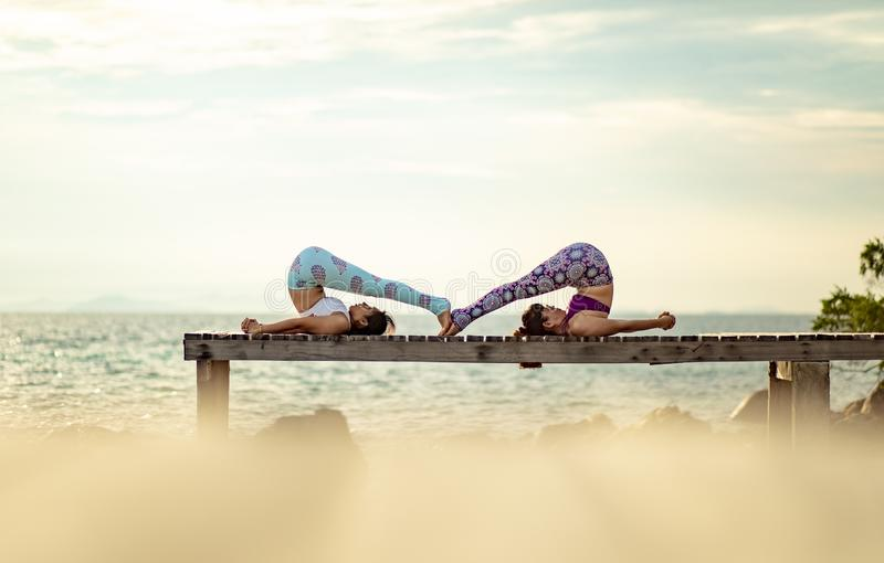 Couples of woman playing yoga pose on beach pier with moring sun royalty free stock photo
