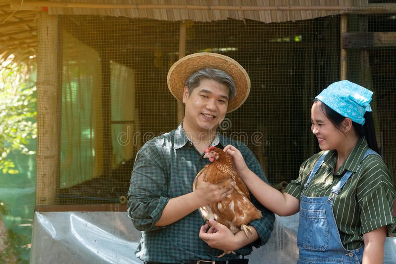 Couples are working at the chicken egg farm. And men are holding hens. Both look happy and healthy stock photo