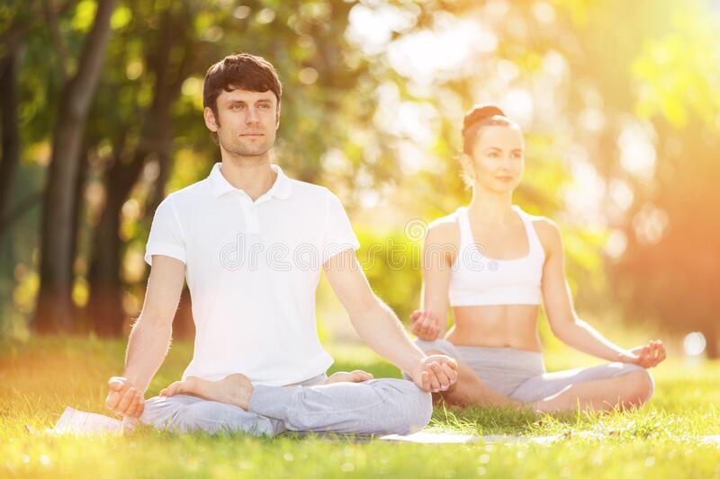 Couples Yoga, man and woman doing yoga exercises, meditate in sunny spring park. Yoga outdoor. Concept of healthy lifestyle and stock photo