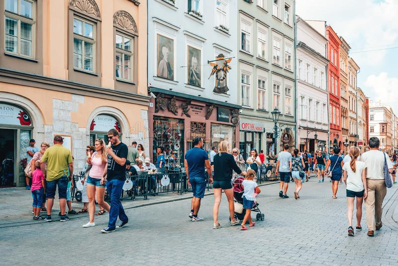 Couples and young families with children walking on busy street in old town Krakow. People enjoying warm summer Sunday by walking, eating ice creams and stock photos