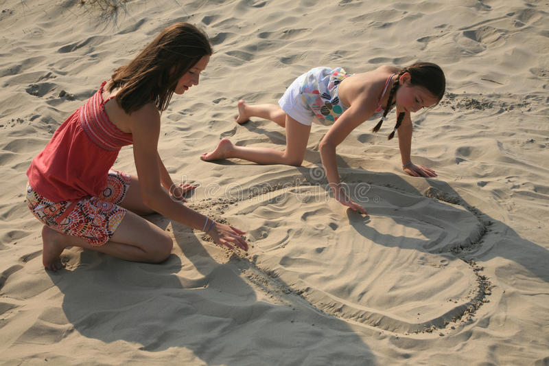 Couples of young girls. Couple of girls at the beach drawing with finger on the sand stock photography