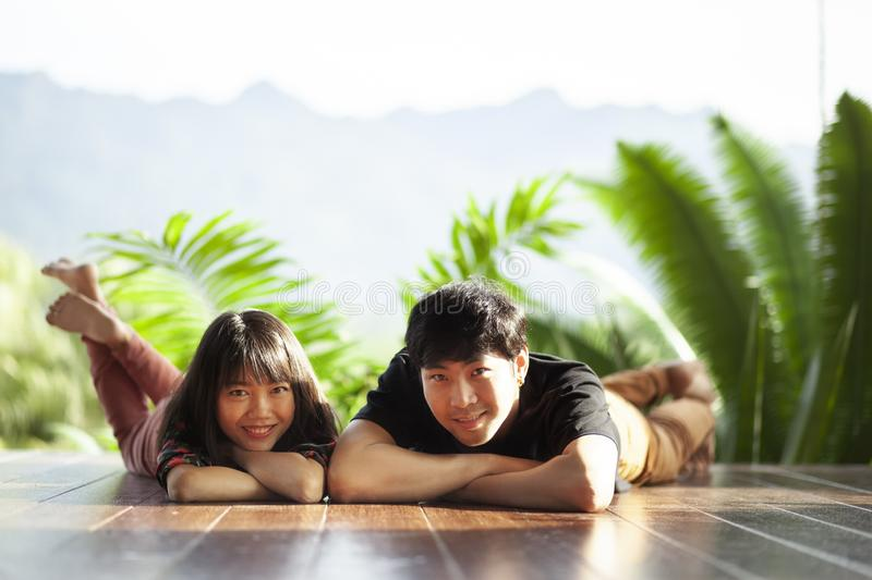 Couples of younger asian man and woman lying with happiness face on home wood floor stock photos