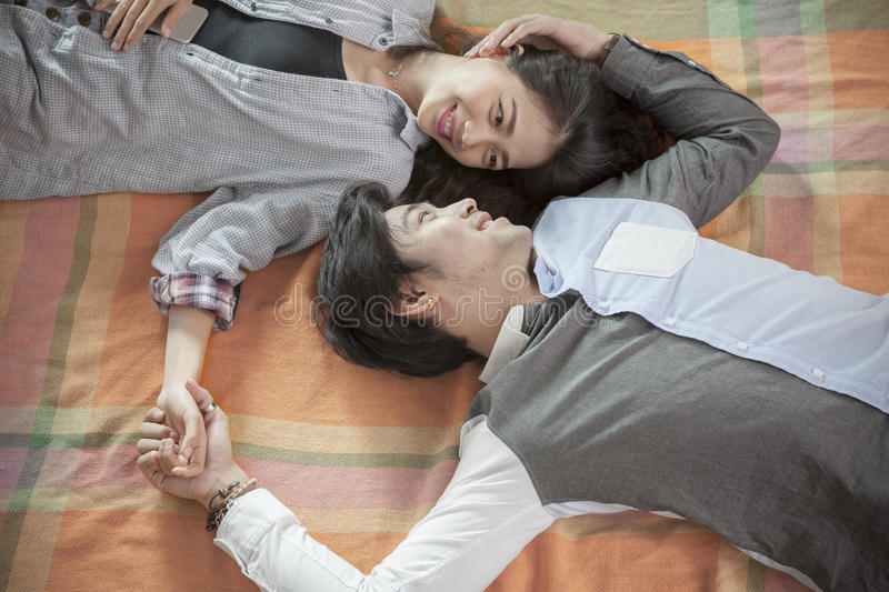 Couples of younger asian man and woman relaxing emotion lying in royalty free stock image