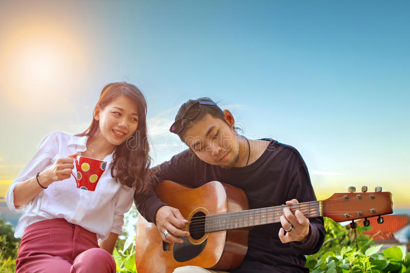 Couples of younger asian man and woman relaxing playing guitar i. Couples of younger asian men and women relaxing playing guitar in park stock photography