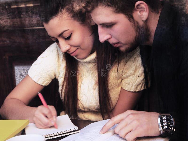 Couplestudents felizes novos no café, vista através de uma janela fotografia de stock royalty free