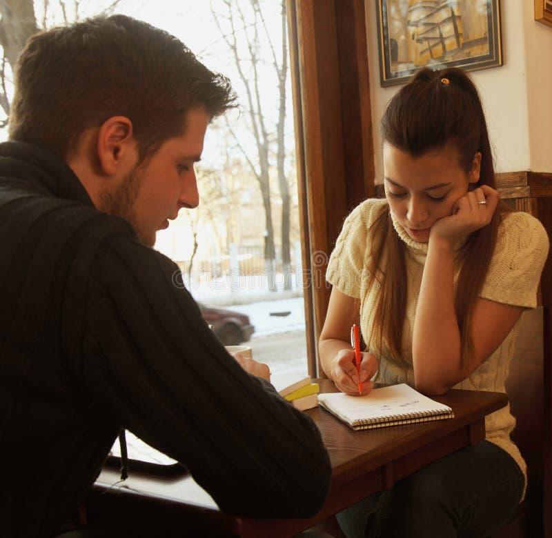 Couplestudents felizes novos no café, vista através de uma janela imagens de stock royalty free