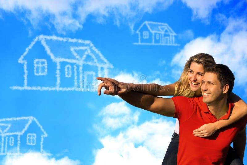 Coupleunder feliz el cielo azul que sueña con una casa. imagen de archivo