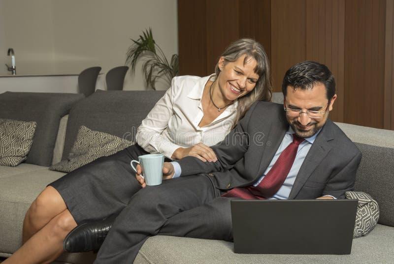 Couplez à la maison dans le formalware avec le fonctionnement de l'homme et l'observation de femme photos stock