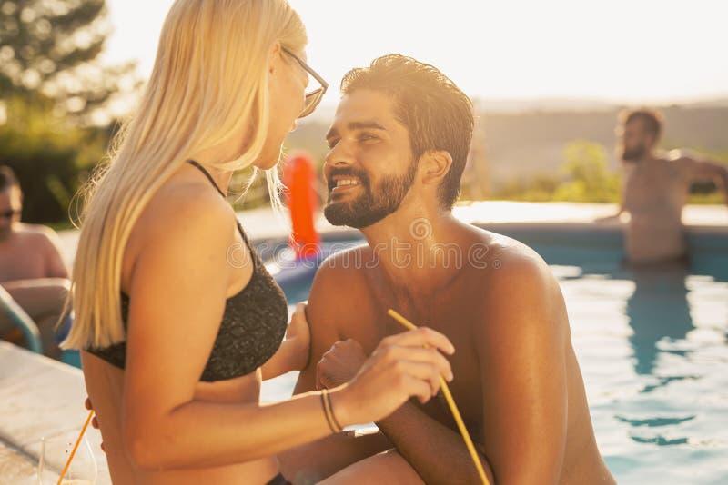 Couplez à une partie de poolside photo stock