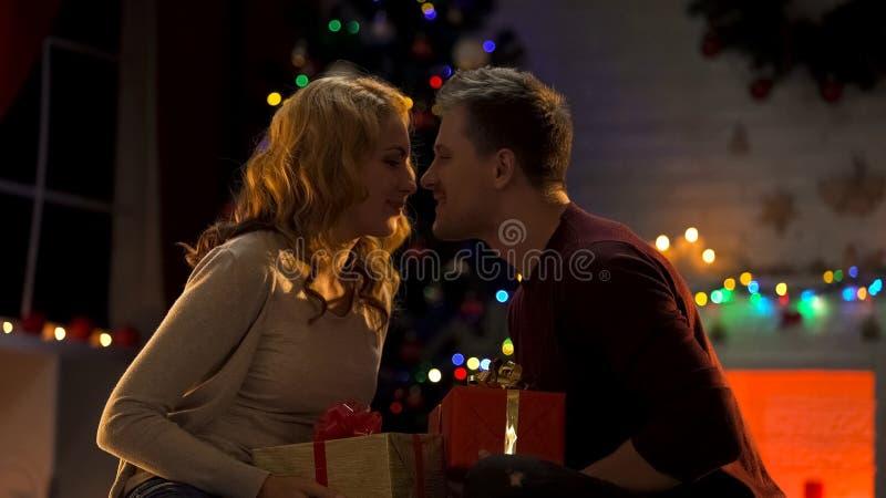 Couplez échanger des cadeaux sous l'arbre de Noël, moment intime, l'atmosphère de fête photographie stock