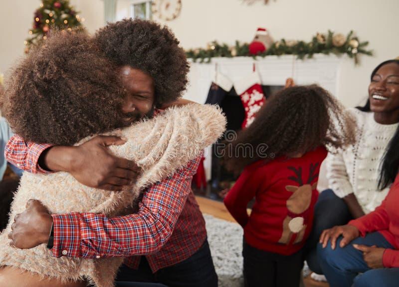 Couplez étreindre comme ils échangent des cadeaux à Noël multi de famille de génération à la maison images stock