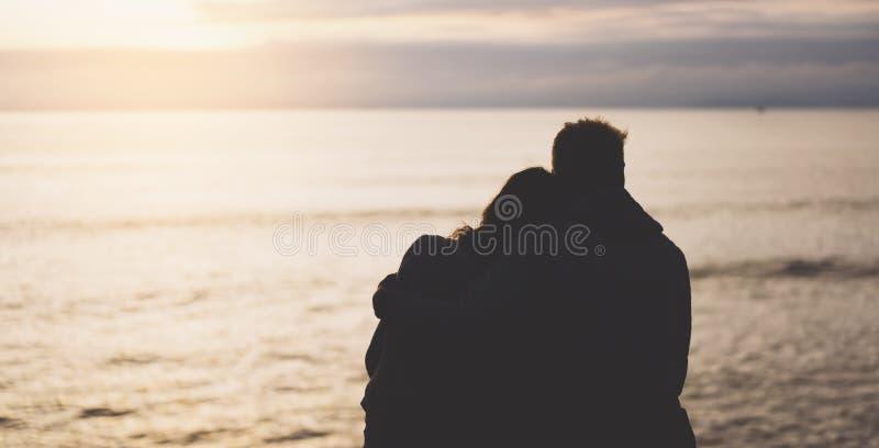 Couplez étreindre sur le lever de soleil d'océan de plage de fond, réunion de concept d'amants, silhouettez deux personnes romant photo stock