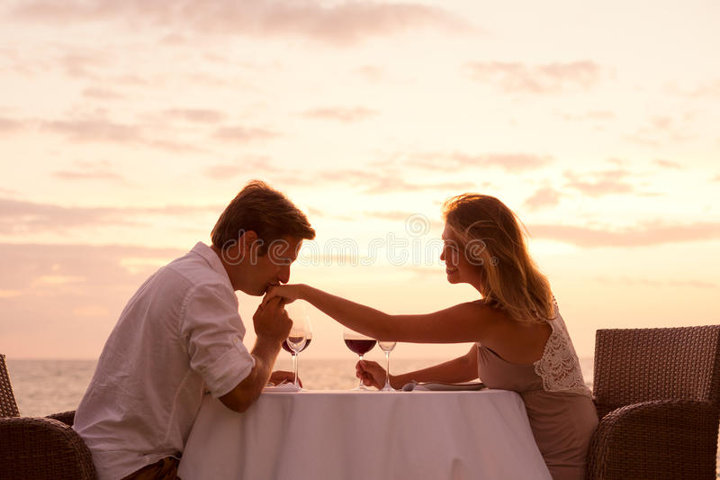 Couplez apprécier le dîner romantique de sunnset sur la plage image stock