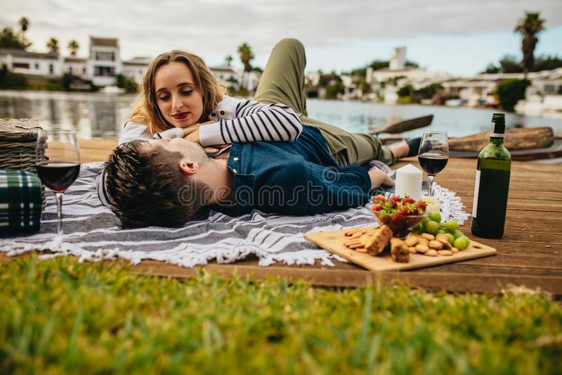 Couplez apprécier leur date près d'un lac photographie stock libre de droits