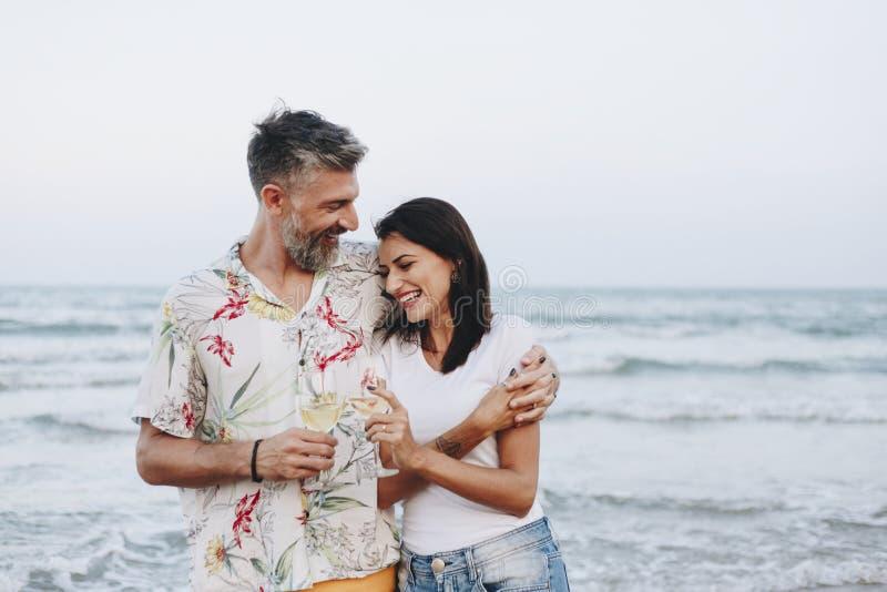 Couplez apprécier un verre de vin par la plage images stock