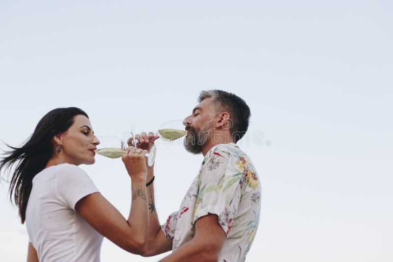 Couplez apprécier un verre de vin par la plage photographie stock