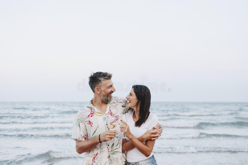 Couplez apprécier un verre de vin par la plage images libres de droits