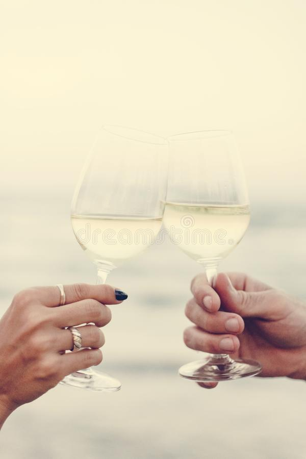 Couplez apprécier un verre de vin par la plage photo libre de droits