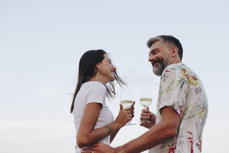 Couplez apprécier un verre de vin par la plage image stock