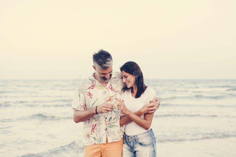 Couplez apprécier un verre de vin par la plage photographie stock libre de droits