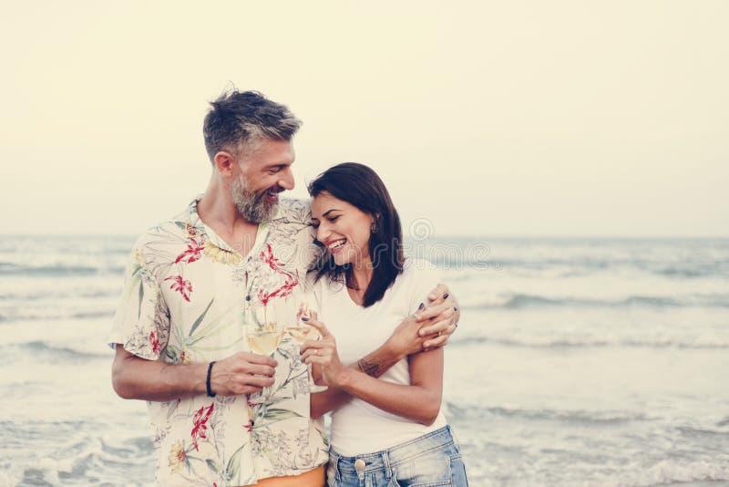 Couplez apprécier un verre de vin par la plage image libre de droits