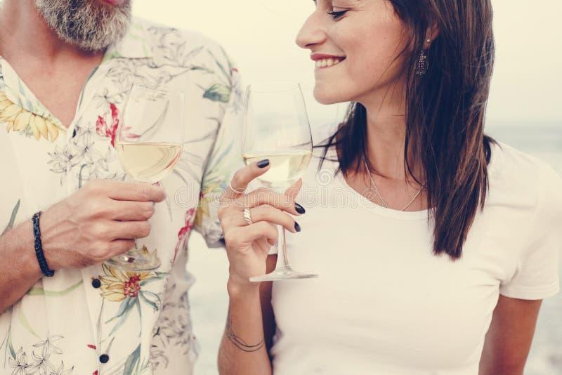 Couplez apprécier un verre de vin par la plage photos libres de droits