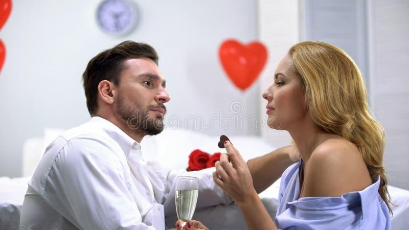 Couplez avoir des préliminaires, manger du chocolat et boire du champagne, appréciant le temps photos stock