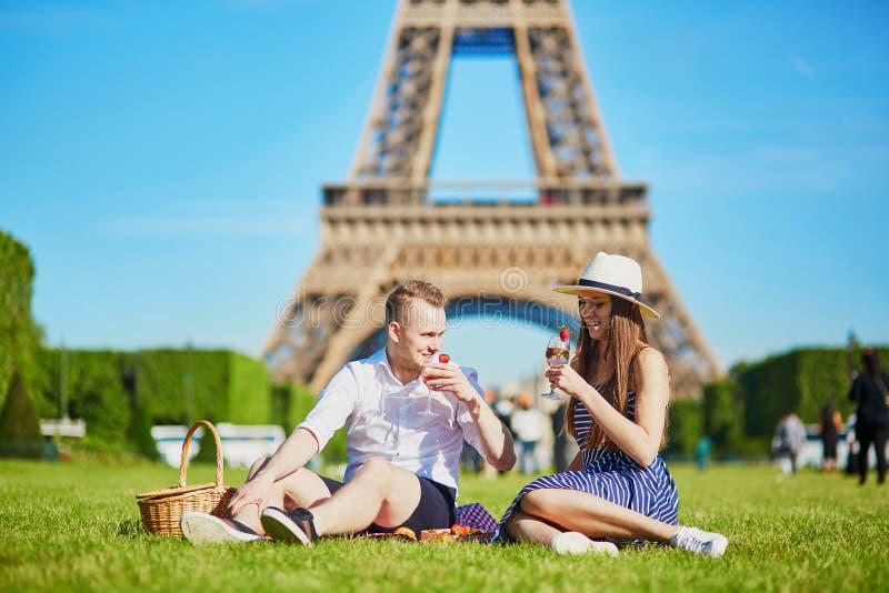 Couplez avoir le pique-nique près de Tour Eiffel à Paris, France photographie stock