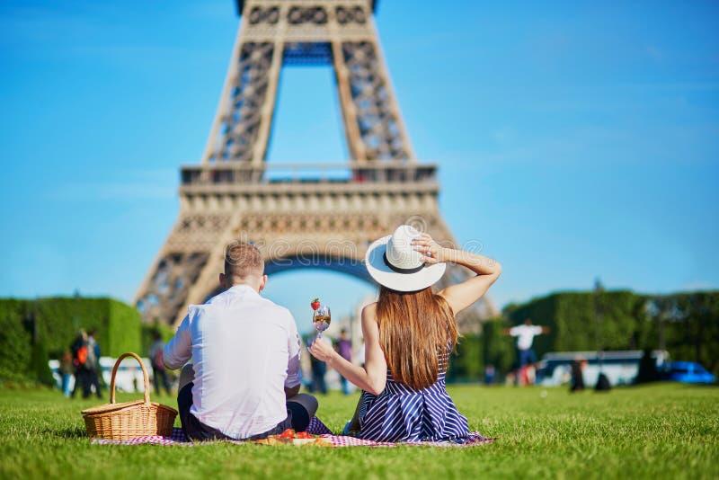 Couplez avoir le pique-nique près de Tour Eiffel à Paris, France photographie stock libre de droits