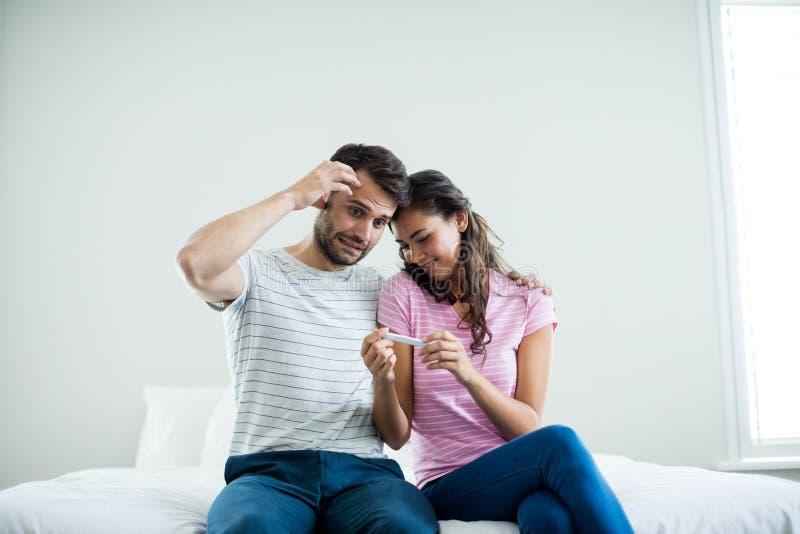 Couplez découvrir des résultats d'un essai de grossesse dans la chambre à coucher photos stock