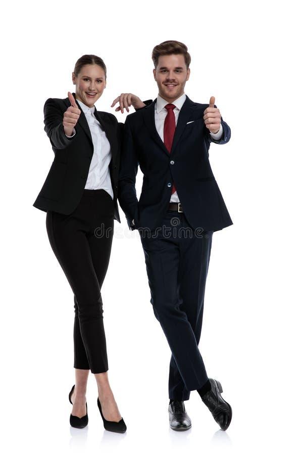 Couplez dans des costumes aimant avec des pouces  images stock