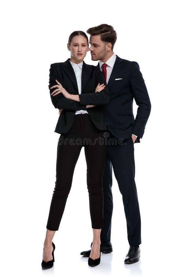 Couplez dans des costumes avec des bras a croisé le chuchotement photos stock