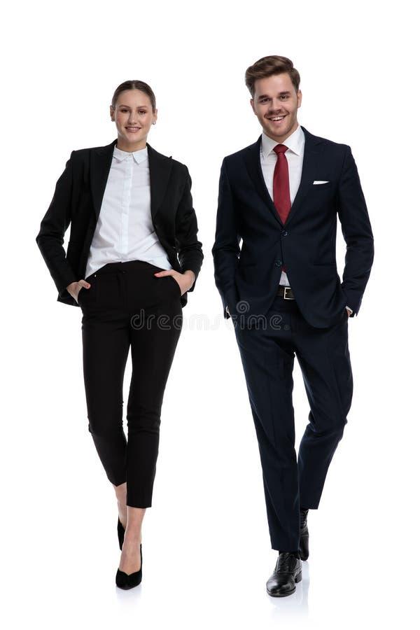 Couplez dans des costumes marchant avec des mains dans des poches photos stock