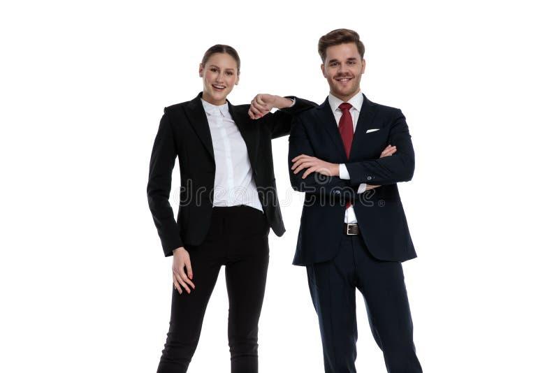 Couplez dans des costumes se tenant avec le maigre de coude sur l'épaule photos libres de droits