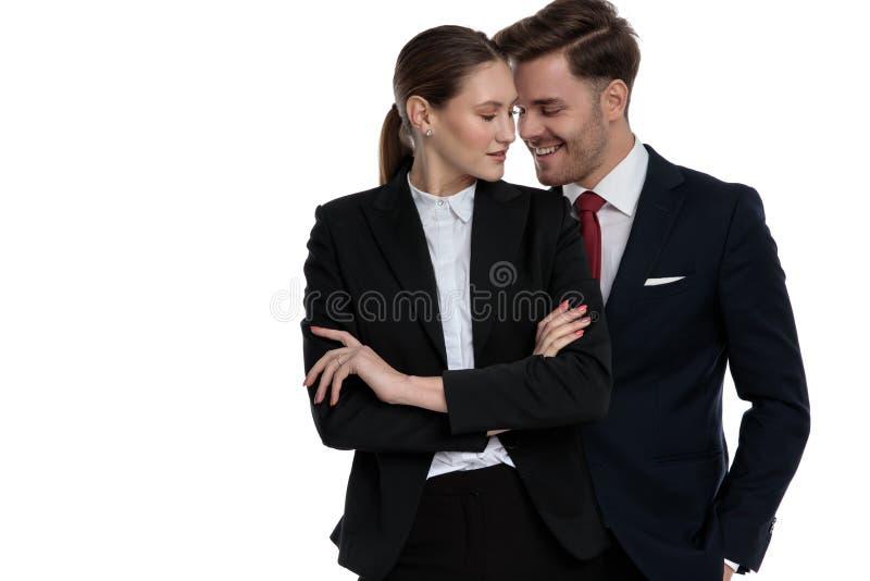 Couplez dans des costumes se tenant ensemble souriants photographie stock libre de droits