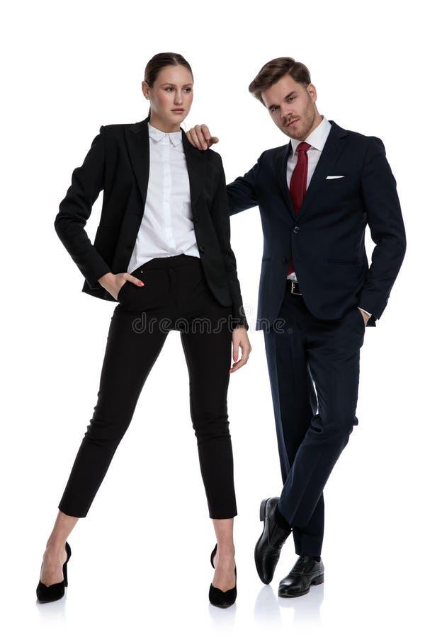 Couplez dans des costumes semblant sérieux photographie stock